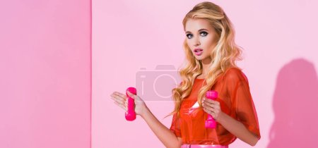 Photo for Panoramic shot of beautiful girl with dumbbells on pink, doll concept - Royalty Free Image