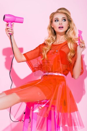 Photo for Beautiful girl with hair dryer and hair brush on pink, doll concept - Royalty Free Image