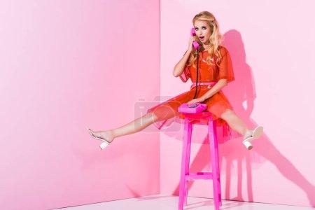 Foto de Hermosa chica sorprendida hablando en el teléfono retro en rosa, concepto de muñeca - Imagen libre de derechos