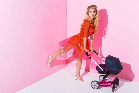 Photo pour Belle fille avec la poussette de bébé sur le rose avec l'espace de copie, concept de poupée - image libre de droit