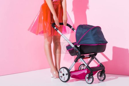Photo for Cropped view of girl with baby stroller on pink, doll concept - Royalty Free Image