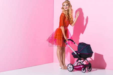 Photo for Beautiful girl with baby stroller waving on pink, doll concept - Royalty Free Image