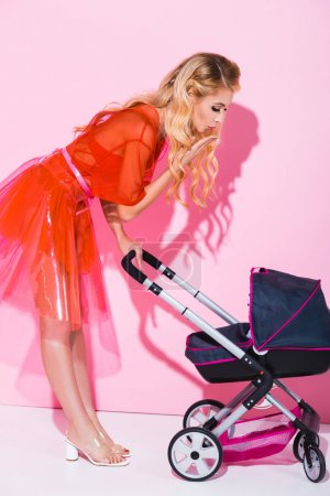 Photo for Beautiful girl with baby stroller on pink, doll concept - Royalty Free Image