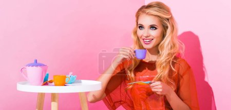 Photo for Panoramic shot of beautiful smiling girl with toy cup on pink, doll concept - Royalty Free Image