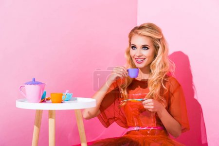 Foto de Beautiful smiling girl with toy cup on pink, doll concept - Imagen libre de derechos