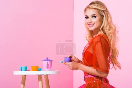 Photo for Beautiful smiling girl with toy cup on pink, doll concept - Royalty Free Image