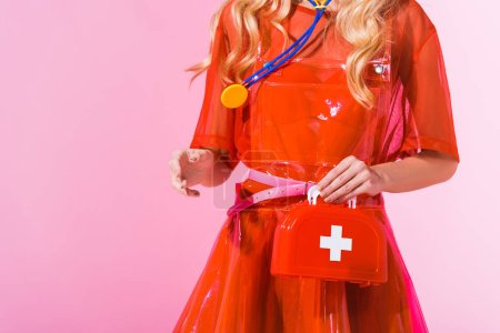 Photo for Cropped view of girl with first aid kit and stethoscope on pink, doll concept - Royalty Free Image