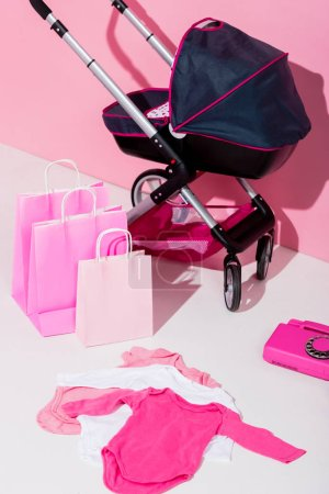 Photo for Baby carriage, shopping bags, bodysuits and telephone on pink - Royalty Free Image
