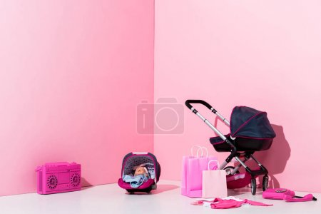 Photo for Baby carriage, doll in baby carrier, shopping bags and boombox on pink - Royalty Free Image