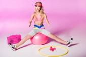 "Постер, картина, фотообои ""girl in sportswear sitting on Fitness Ball near sport equipment on pink, doll concept"""