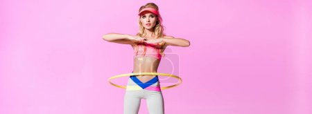 Photo for Panoramic shot of beautiful girl in sportswear training with hoop isolated on pink, doll concept - Royalty Free Image
