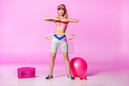 Photo pour Fille dans sportswear et formation de chapeau de visière de soleil avec le cerceau sur le rose, concept de poupée - image libre de droit
