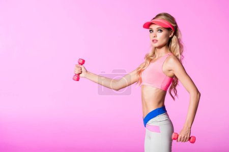 Photo for Beautiful girl training with dumbbells isolated on pink, doll concept - Royalty Free Image