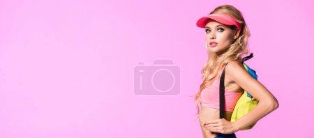 Photo pour Tir panoramique de la belle fille dans le chapeau de visière de soleil avec le sac à dos d'isolement sur le rose, concept de poupée - image libre de droit