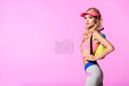beautiful girl in sun visor hat with backpack isolated on pink, doll concept