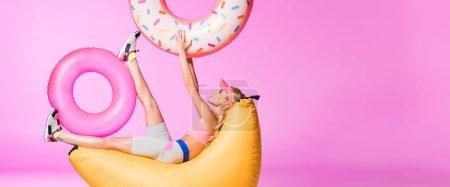 Photo pour Tir panoramique de fille sur la chaise de sac de harigo avec les anneaux gonflables de natation sur le rose, concept de poupée - image libre de droit
