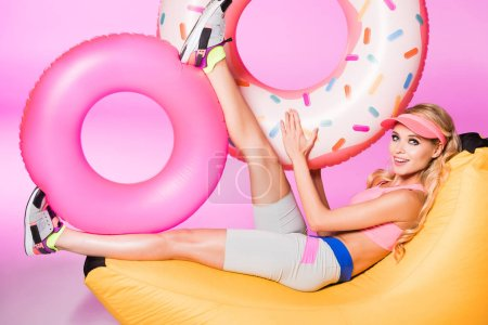 Foto de Atractiva chica feliz en silla de bolsa de frijoles con anillos de baño inflables en rosa, concepto de muñeca - Imagen libre de derechos