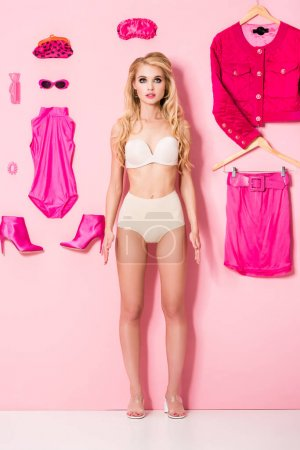 Photo for Beautiful girl in underwear near flat lay of clothes and accessories on pink, doll concept - Royalty Free Image
