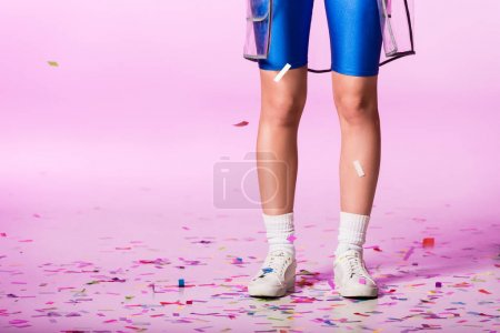 Photo for Cropped view of girl in sportswear on pink with confetti, doll concept - Royalty Free Image