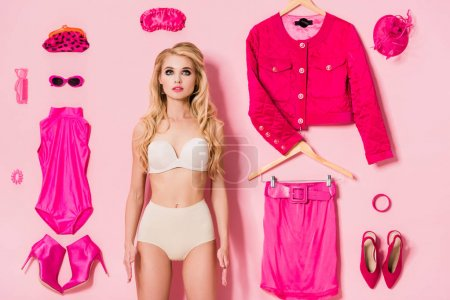 Photo for Pretty girl in underwear near flat lay of clothes and accessories on pink, doll concept - Royalty Free Image