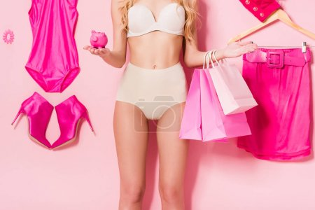 Photo for Cropped view of girl in underwear with piggy bank and shopping bags near flat lay of clothes and accessories on pink, doll concept - Royalty Free Image