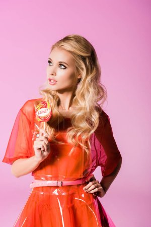 Photo for Beautiful stylish girl posing with lollipop on pink, doll concept - Royalty Free Image