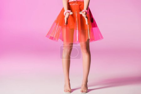 Photo for Cropped view of girl in handcuffs on pink, doll concept - Royalty Free Image