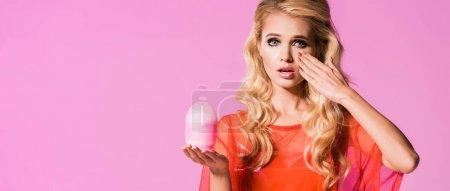 Foto de Foto panorámica de hermosa chica sorprendida posando con lámpara aislada en rosa, concepto de muñeca - Imagen libre de derechos
