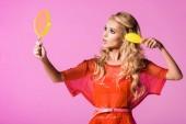 "Постер, картина, фотообои ""beautiful girl looking at hand mirror and brushing hair isolated on pink, doll concept"""