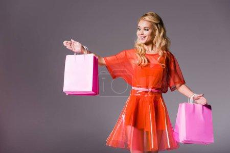 Photo pour Belle fille avec des sacs à provisions sur le gris, concept de poupée - image libre de droit