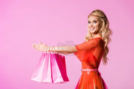 Photo for Beautiful girl with shopping bags isolated on pink, doll concept - Royalty Free Image