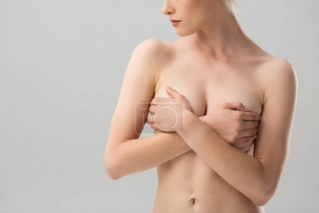 partial view of sexy naked girl covering breast isolated on grey