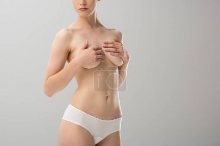 cropped view of sexy topless girl in panties covering breast isolated on grey