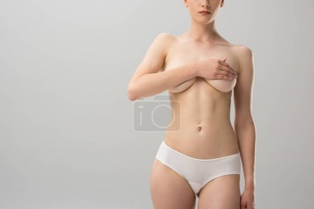 partial view of sexy topless girl in panties covering breast isolated on grey