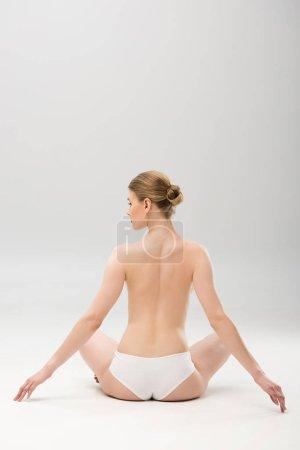 Photo pour Vue arrière de la jeune femme en culotte assise sur gris - image libre de droit