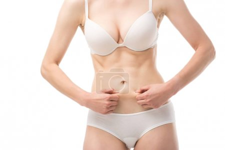 Photo for Cropped view of woman in underwear holding skin on belly isolated on white - Royalty Free Image