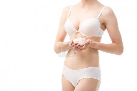 Photo pour Vue recadrée de jeune femme dans des sous-vêtements retenant la crème cosmétique d'isolement sur le blanc - image libre de droit