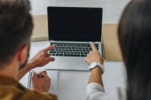 selective focus of man and woman pointing with fingers at screen of laptop