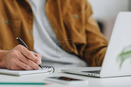 Photo for Cropped view of man writing in notebook with pen - Royalty Free Image