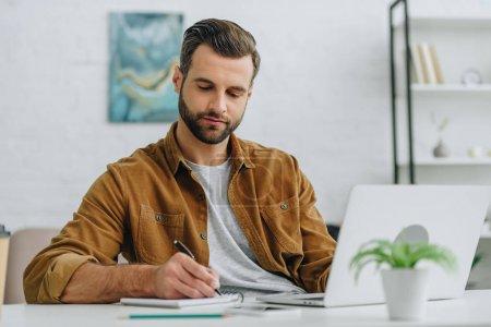 Photo pour Bel homme écrit dans un cahier avec stylo dans l'appartement - image libre de droit