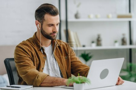 Photo for Handsome man using laptop and listening music in apartment - Royalty Free Image