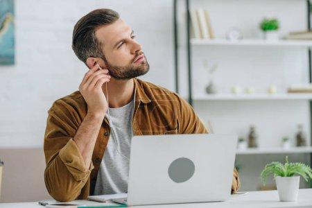 Photo pour Bel homme écoutant de la musique et regardant loin dans l'appartement - image libre de droit