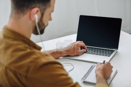 Photo for Selective focus of man listening music, writing in notebook and using laptop - Royalty Free Image