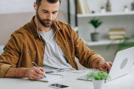 Photo pour Bel homme écoutant de la musique, écrivant dans un cahier et utilisant un ordinateur portable - image libre de droit