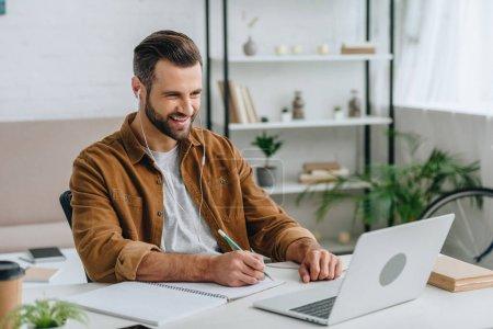 Photo pour Homme beau écouter de la musique, en utilisant un ordinateur portable et l'écriture dans un cahier - image libre de droit