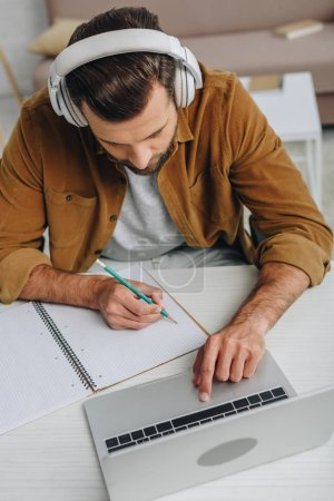 Photo for High angle view of man listening music, writing in notebook and using laptop - Royalty Free Image