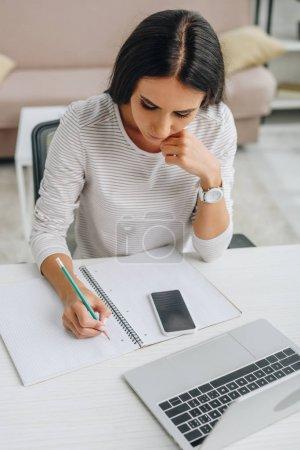 Photo pour Vue d'angle élevé de la belle écriture de femme dans le cahier avec le crayon - image libre de droit