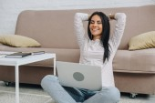 beautiful woman with closed eyes smiling and holding laptop