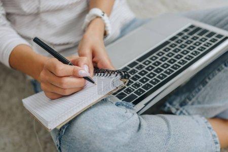 Photo pour Vue recadrée de femme écrivant dans un cahier et tenant un ordinateur portable - image libre de droit