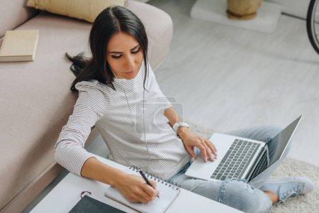 Photo pour Vue d'angle élevé de la femme avec des écouteurs écrivant dans le cahier et l'ordinateur portatif de fixation - image libre de droit